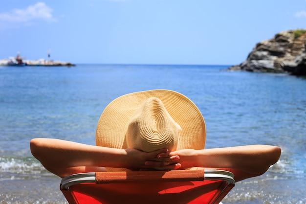 Viaggio, vocazione, concetto di vacanza. la donna in cappello è sdraiata sulla sedia a sdraio sulla spiaggia dal mare.