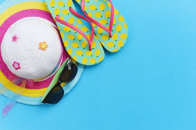 Concetto / oggetti della parete di viaggio accessori di viaggio di estate con le infradito del cappello degli occhiali da sole per il viaggiatore sulla parete blu