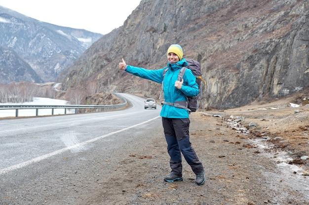 Donna di viaggio autostop. bella giovane femmina autostoppista sulla strada durante il viaggio di vacanza in montagna
