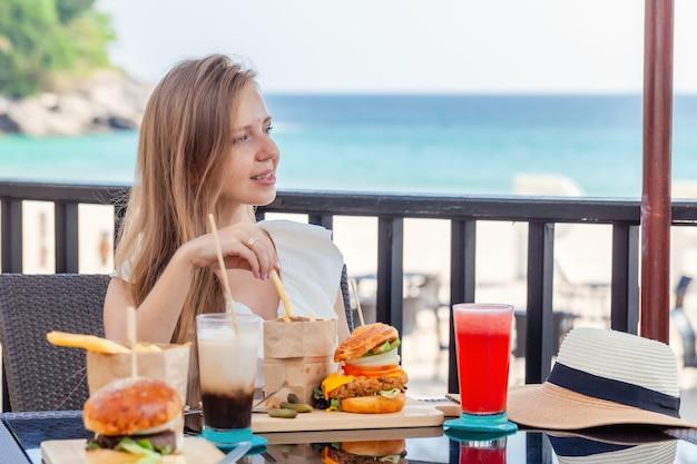 Donna di viaggio con hamburger fast food caffè e bevande succhi di frutta al caffè all'aperto