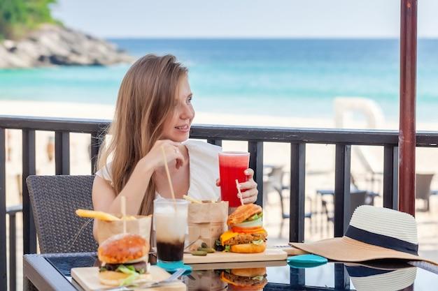 Donna di viaggio con hamburger di fast food caffè e succhi di frutta al caffè all'aperto