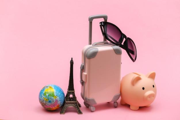 Concetto viaggiato. mini valigia da viaggio in plastica con occhiali da sole e statuetta della torre eiffel, globo, salvadanaio su sfondo rosa.