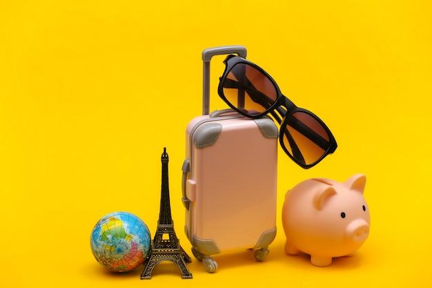Concetto viaggiato. mini valigia da viaggio in plastica con occhiali da sole e statuetta della torre eiffel, globo, salvadanaio su sfondo giallo.