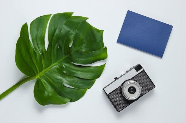 Viaggiato minimalista ancora in vita. foglia di monstera, fotocamera retrò, passaporto su sfondo bianco.