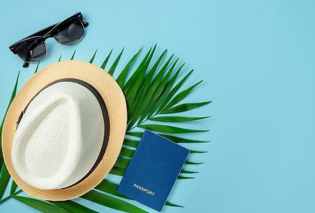 Accessori per viaggiatori e foglia di palma su sfondo blu. in alto, copia spazio.