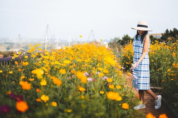 Donna asiatica del viaggiatore che fa un giro turistico sul giacimento di fiore giallo in giardino a phetchabun tailandia