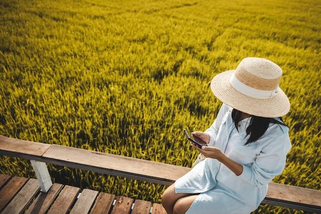 Donna asiatica del viaggiatore che per mezzo del telefono cellulare sul giacimento del riso nell'azienda agricola a nakhon nayok tailandia