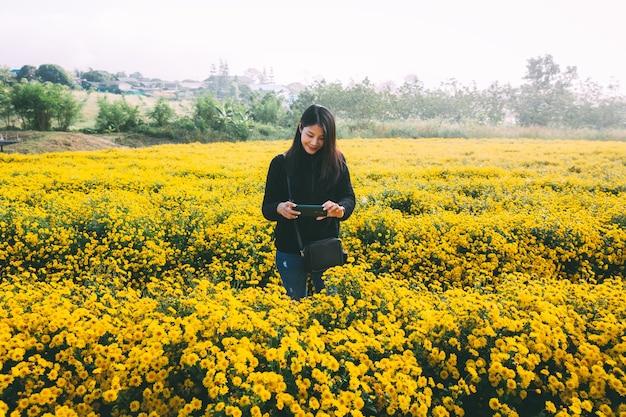 Donna asiatica del viaggiatore che per mezzo del telefono cellulare sul giacimento di fiore giallo in giardino a chiang mai thailandia
