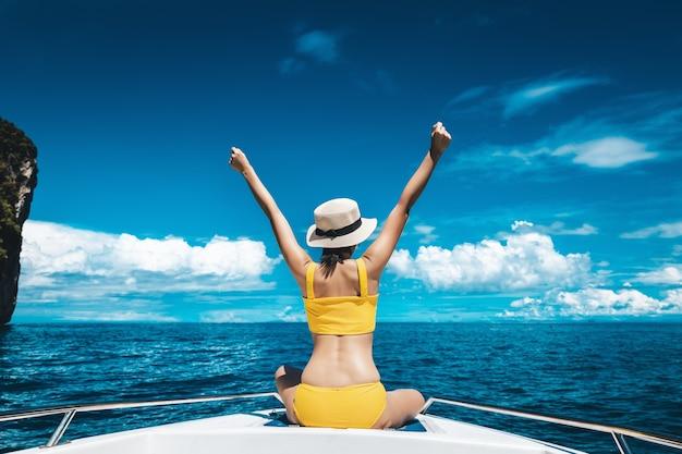 La donna asiatica del viaggiatore con il bikini ed il cappello si rilassa sulla barca in maya bay phuket tailandia