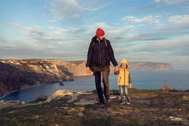 Il bambino del ragazzo viaggiatore con il padre cammina su una scogliera in riva al mare in giacche con le spalle al tramonto
