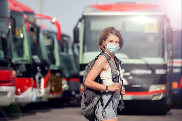 Viaggiatore alla stazione degli autobus all'aperto. donna con zaino e maschera medica in attesa di un autobus. concetto di viaggio e turismo