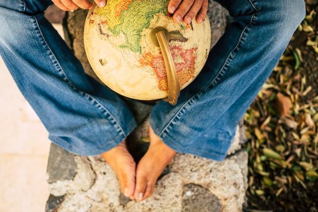 Gambe e mani caucasiche del viaggiatore con una sfera del globo terrestre nel mezzo che sceglie la destinazione di vacanza del viaggio successivo che arrotonda la mappa viaggio esplorare e concetto di giovani persone moderne