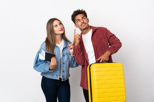 Coppia di viaggiatori in possesso di una valigia su blu che punta con il dito indice una grande idea