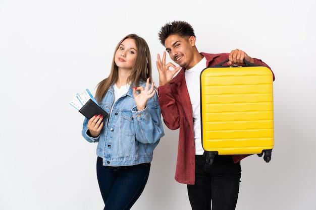 Coppie del viaggiatore che tengono una valigia sull'azzurro che mostra un segno giusto con le dita