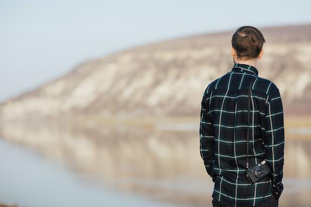 Viaggiatore che gode della splendida vista sulla montagna e sul fiume
