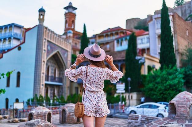 Ragazza viaggiatrice sullo sfondo dei famosi bagni di zolfo nel quartiere abanotubani della vecchia città di tbilisi, georgia
