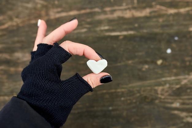Ragazza viaggiatore in guanti neri tenere in mano marshmallow a forma di cuore