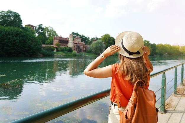 Ragazza viaggiatrice che tiene il cappello alla scoperta del castello nascosto nel parco. giovane donna che si rilassa e respira sul fiume di passeggiata.