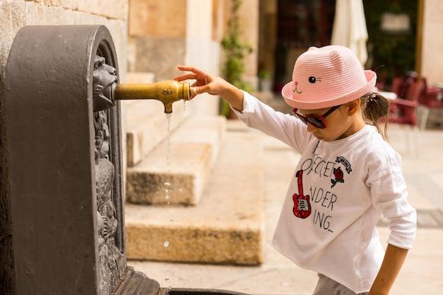 Ragazza del viaggiatore nella città vecchia vicino al rubinetto dell'acqua medievale