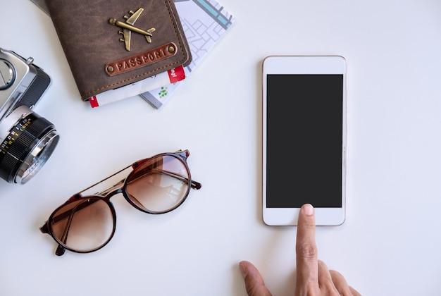 Smart phone della tenuta del viaggiatore con il passaporto e la mappa, concetto di viaggio