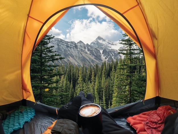 Viaggiatore sdraiato e tenendo una tazza di caffè in tenda gialla e godersi la vista della foresta e della montagna nel parco nazionale del campeggio