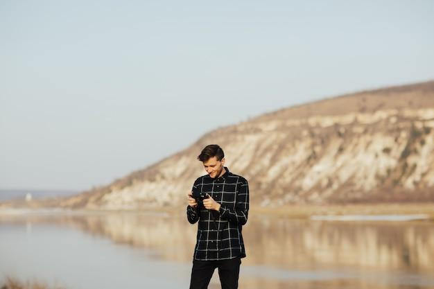 Uomo del viaggiatore che tiene la retro macchina fotografica della foto con la montagna e il fiume