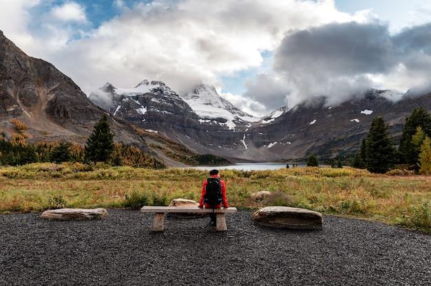Uomo del viaggiatore che si siede sulla spiaggia con il monte assiniboine e il lago magog nel parco provinciale