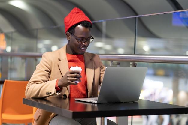 Uomo viaggiatore seduto al bar in aeroporto lavora sul computer portatile in attesa di un imbarco bere caffè