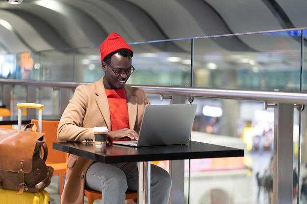 Uomo viaggiatore seduto al tavolino del bar in aeroporto lavora in remoto su laptop in attesa di un volo