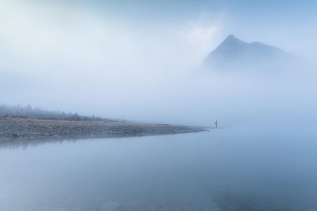 Uomo viaggiatore in piedi da solo nella nebbia blu con montagne rocciose in riva al lago al mattino