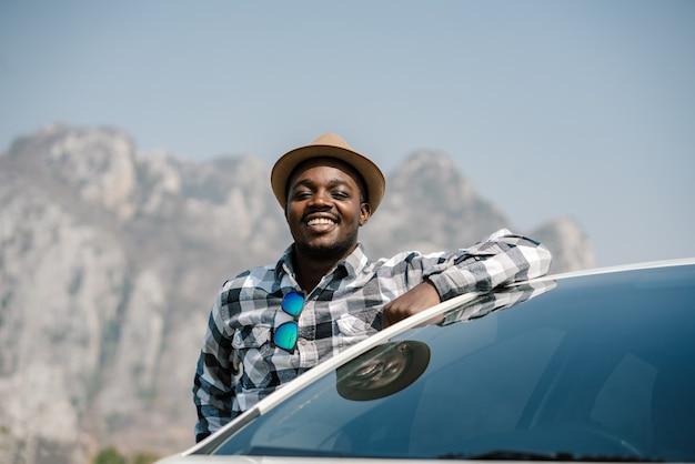Uomo del viaggiatore in piedi con la macchina sulle montagne
