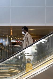 Uomo viaggiatore si leva in piedi sulla scala mobile in aeroporto indossare maschera facciale covid concetto di trasporto