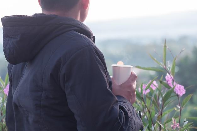 Uomo del viaggiatore che indossa un maglione e che tiene una tazza di caffè caldo