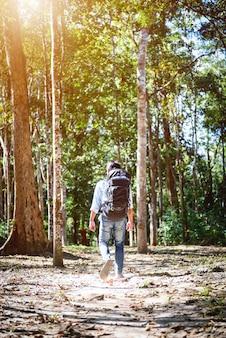 Uomo del viaggiatore con uno zaino nella foresta, concetto di stile di vita felice