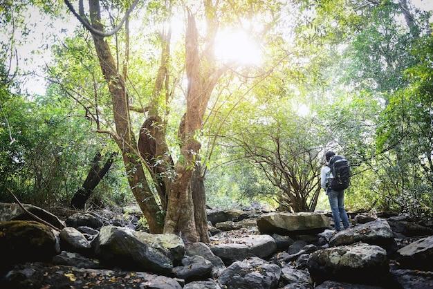 Uomo del viaggiatore con uno zaino nella foresta, concetto di stile di vita felice Foto Premium