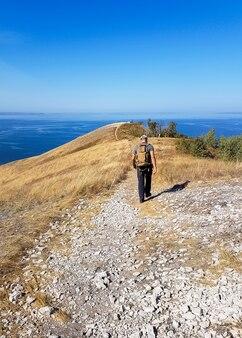Uomo del viaggiatore con lo zaino che cammina al bordo di una collina