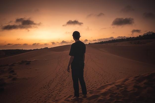 Uomo viaggiatore con cappuccio in piedi sulla duna al tramonto. mui ne, vietnam