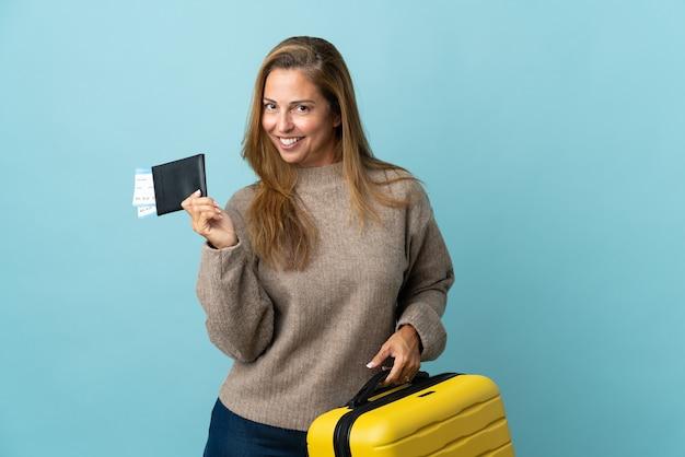 Donna di mezza età del viaggiatore che tiene una valigia isolata sull'azzurro in vacanza con la valigia e il passaporto