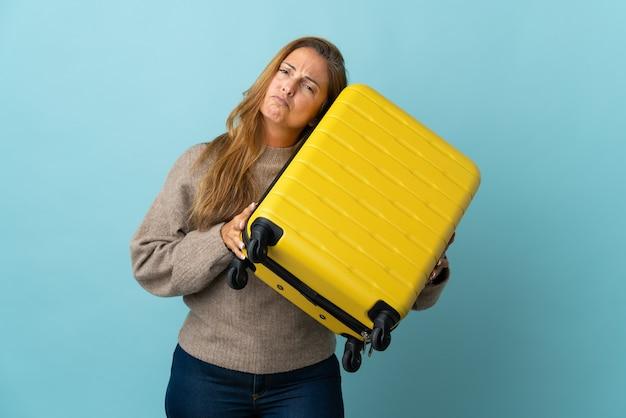 Donna di mezza età del viaggiatore che tiene una valigia isolata sull'azzurro in vacanza con la valigia di viaggio e infelice