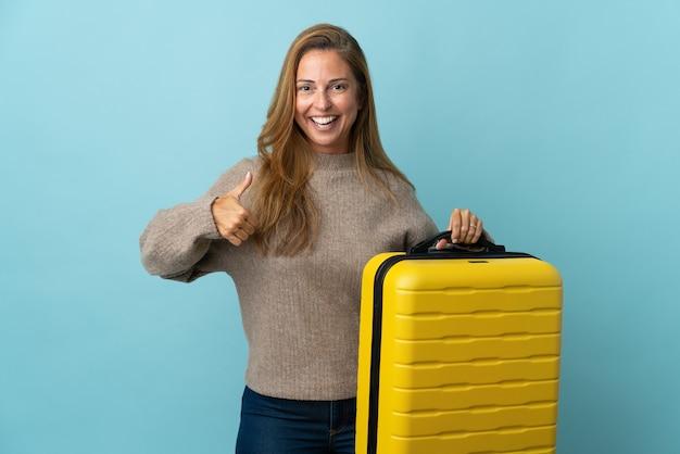 Donna di mezza età del viaggiatore che tiene una valigia isolata sull'azzurro in vacanza con la valigia di viaggio e con il pollice in su