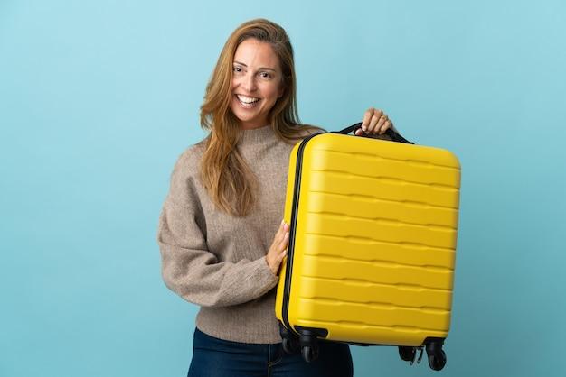 Donna di mezza età del viaggiatore che tiene una valigia isolata sull'azzurro in vacanza con la valigia di viaggio