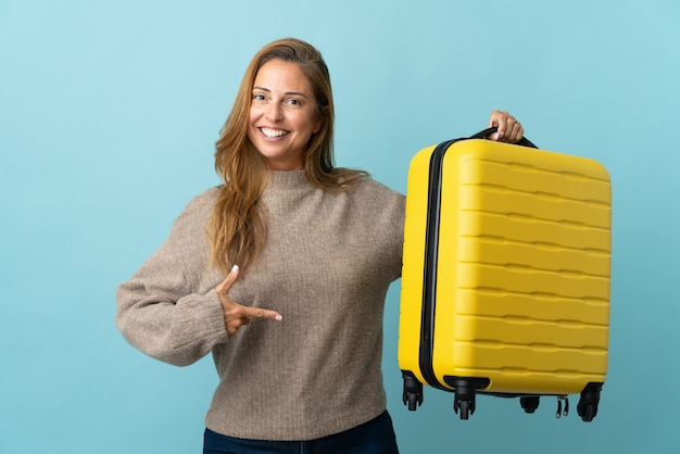 Donna di mezza età del viaggiatore che tiene una valigia isolata sulla parete blu in vacanza con la valigia di viaggio