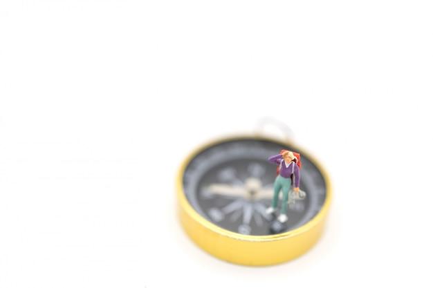 La miniatura del viaggiatore calcola la gente con lo zaino che sta sulla bussola dorata su fondo bianco.