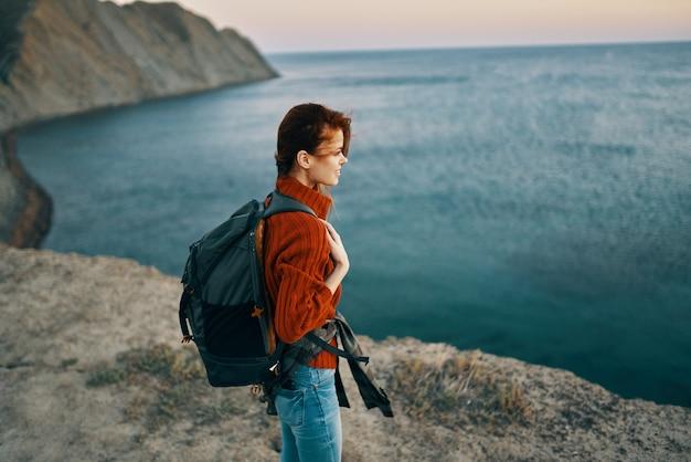 Un viaggiatore in montagna gesticola con le mani vicino al mare al tramonto del paesaggio autunnale