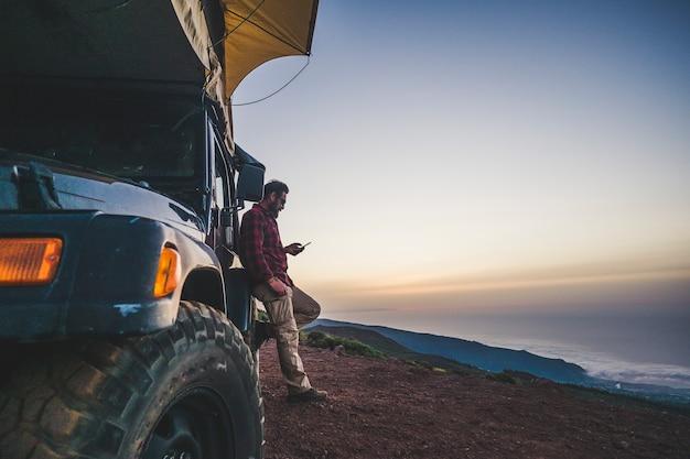 Viaggiatori con concetto di auto e campeggio - l'uomo solitario usa il telefono cellulare per connettersi a internet fuori dal suo veicolo - montagna e natura all'aperto intorno - godendosi la libertà e una vacanza alternativa