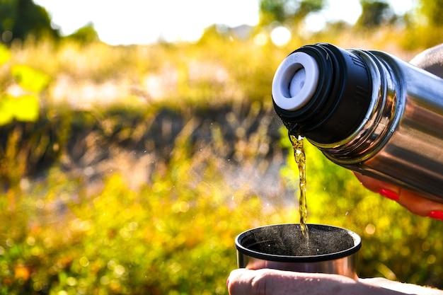 Viaggiatore che versa tè caldo dal thermos alla tazza in autunno foresta caduta all'aperto. picnic estivo autunnale. copia spazio