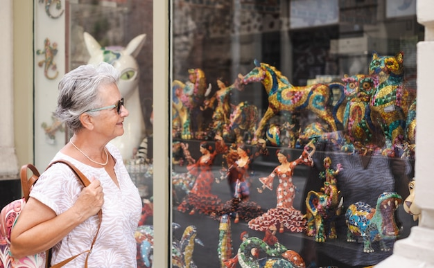 Viaggiatore donna anziana in visita a barcellona alla ricerca di creazioni artistiche nella vetrina di un negozio