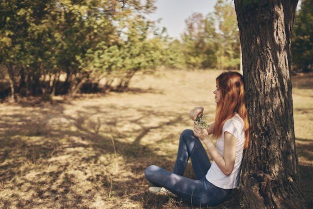 Il viaggiatore si siede vicino a un albero all'aperto nella foresta in jeans e maglietta.