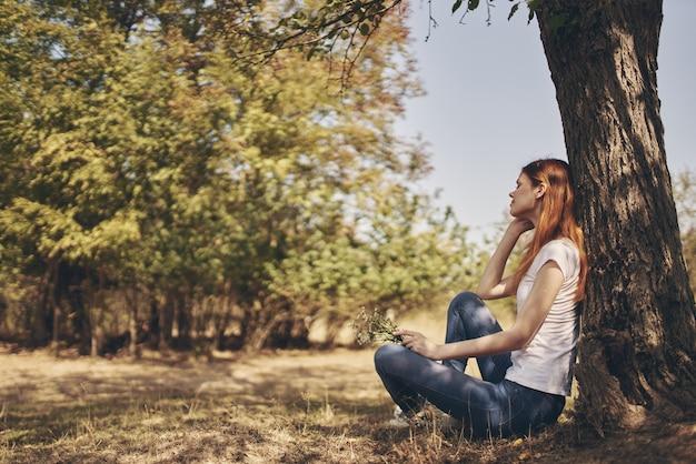 Il viaggiatore si siede vicino a un albero all'aperto nella foresta in jeans e una t-shirt.