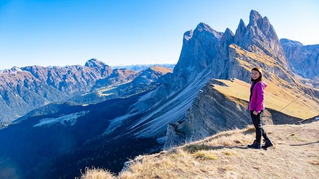 Viaggiatore in piedi con vista del paesaggio a seceda, val gardena, dolomiti, italy